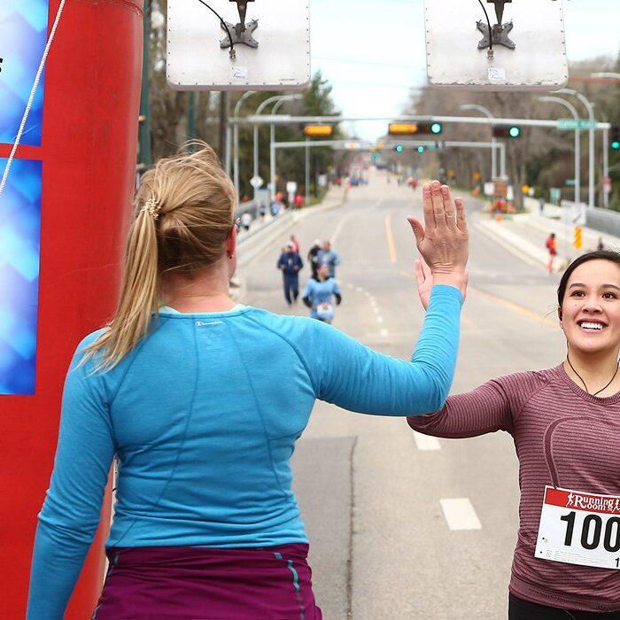 female runner high-fiving race volunteer at finish line
